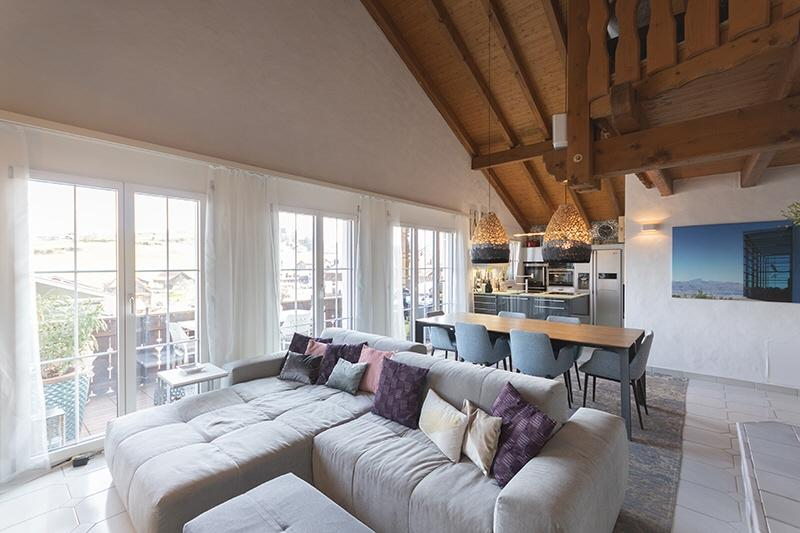 Helles Wohn-Esszimmer mit Cheminée und hohen Decken