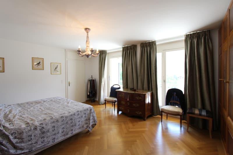 Spacieuse chambre à coucher comprenant des armoires encastrées